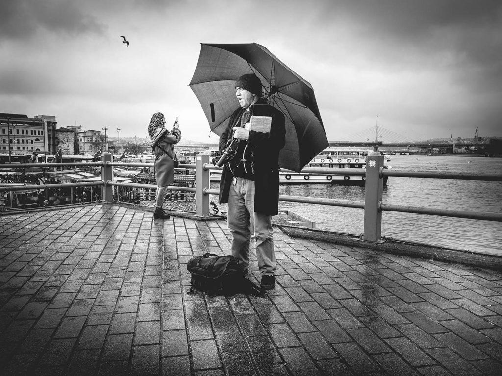 Ein Fotograf steht im Regen und wartet auf Kundschaft