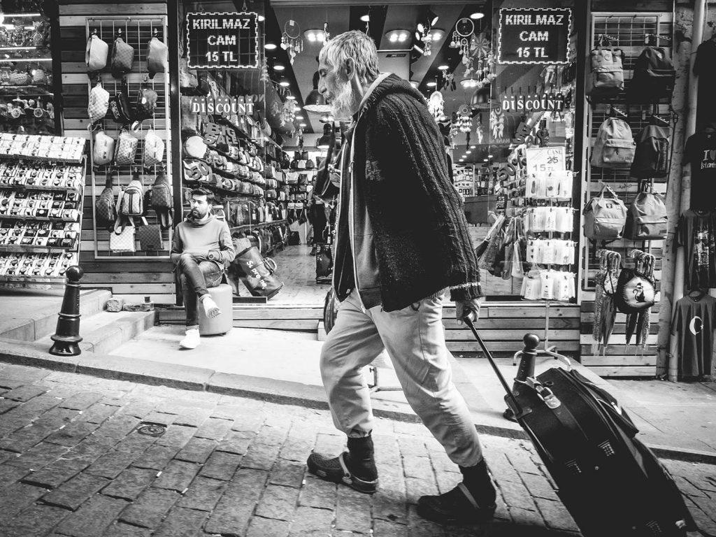 Ein alter Mann geht eine steile Straße hinauf und zieht einen Koffer hinter sich her.