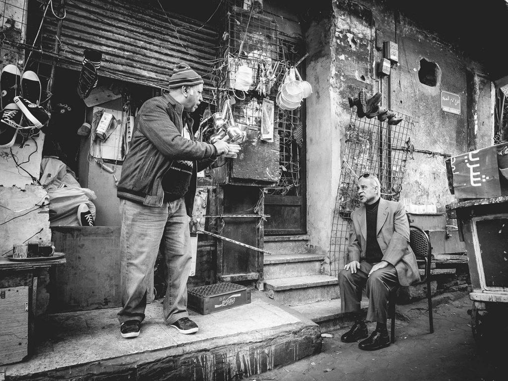 Zwei Männer unterhalten sich auf der Straße vor einem Geschäft.