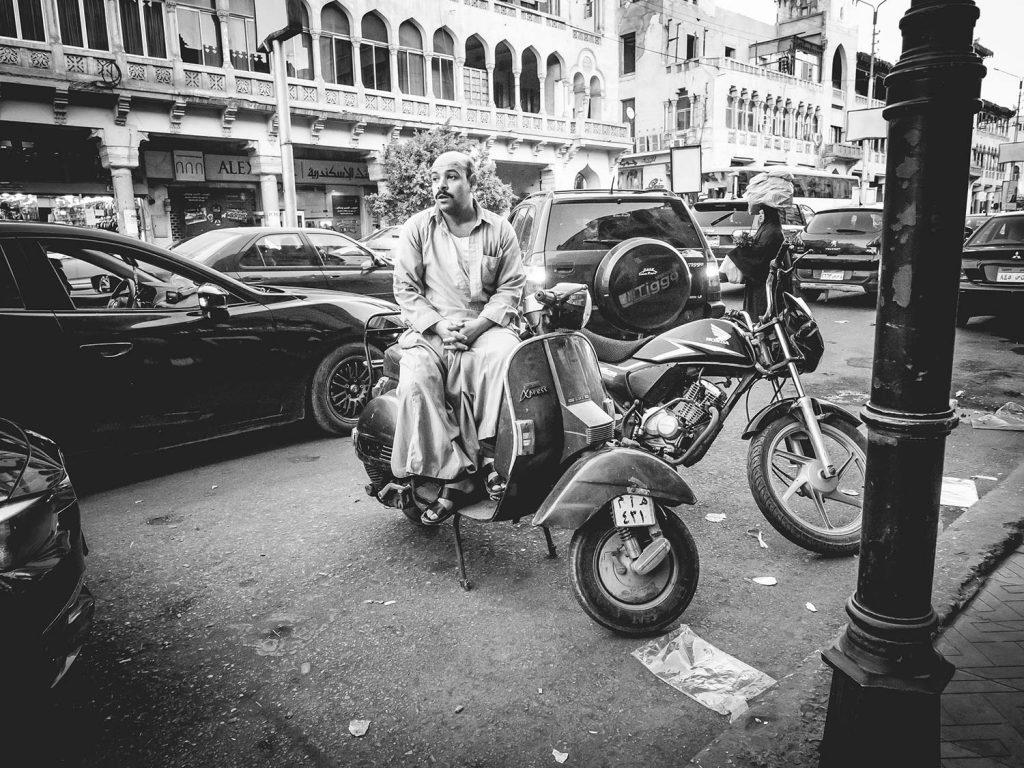 Auf der Straße parken Motorroller. Ein Mann sitzt auf einem der Roller und schaut die Straße hinab.
