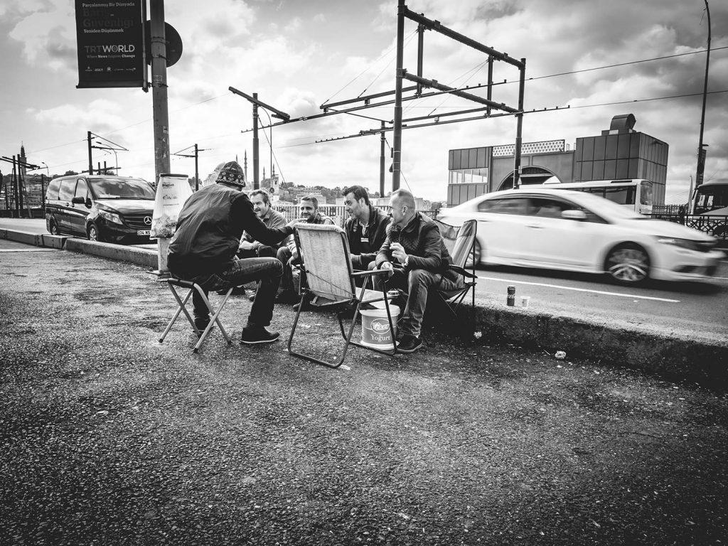Männer sitzen auf einer Brücke und essen.